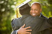 African American Father hugging his son graduation day