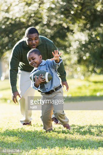African American father and son playing football
