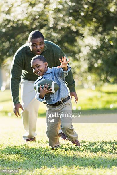 Afro-americano pai e filho Jogando futebol