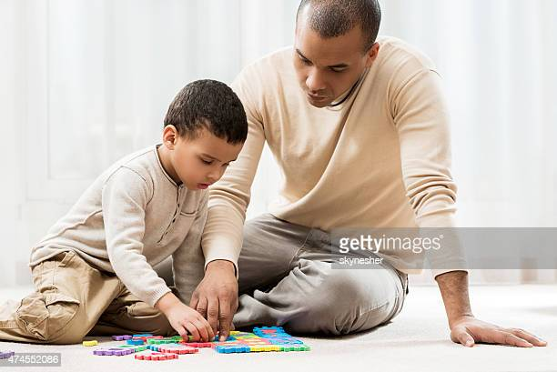 African American father and son playing with puzzles at home.