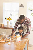 Front view of African American father and son rolling out cookie dough in kitchen at home