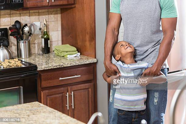 African American father and son standing in kitchen