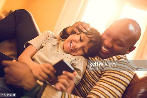 Afro-americano pai e filho mensagens de texto no telefone celular.