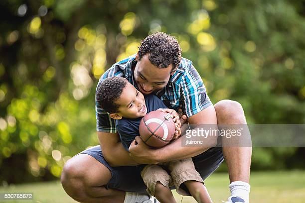 Jeune afro-américaine de père et fils jouer football en plein air