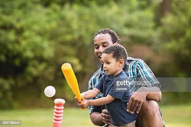 Jeune afro-américaine de père et fils jouant pas ballon en plein air