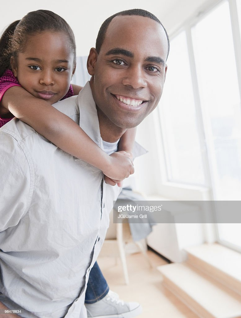 African American father carrying daughter on back : Stock Photo