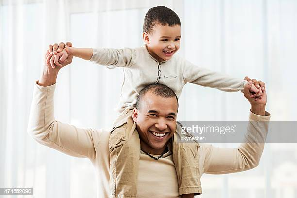 African American father carrying his son on shoulders at home.