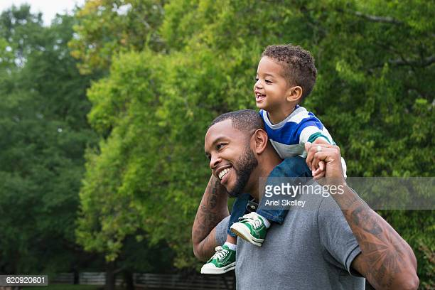 African American father carrying son outdoors