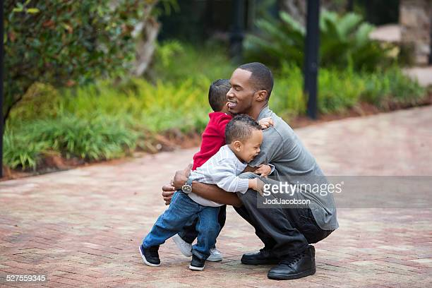 African American father kneels and holds his twin toddlers