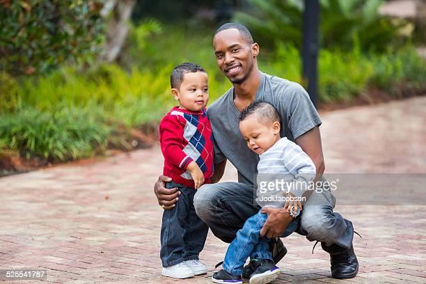 Père afro-américain kneels au rez-de-chaussée, avec son bébé avec lits jumeaux