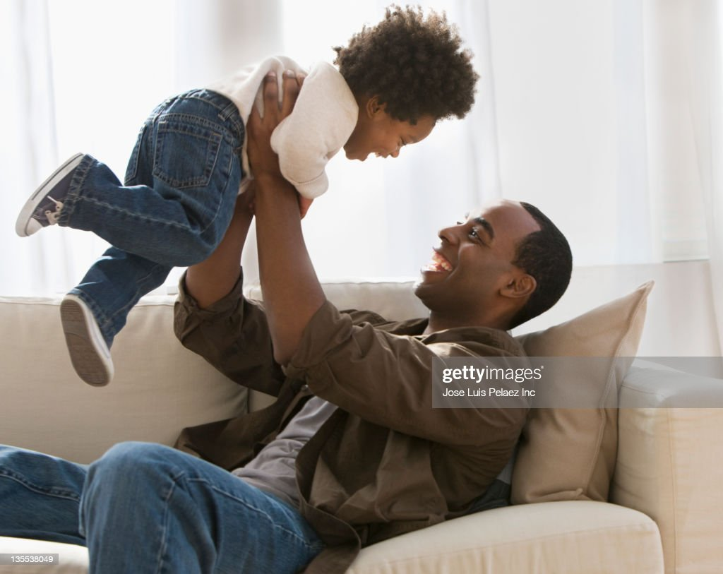 African American father lifting son : Stock Photo