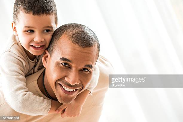 African American father piggybacking his son.