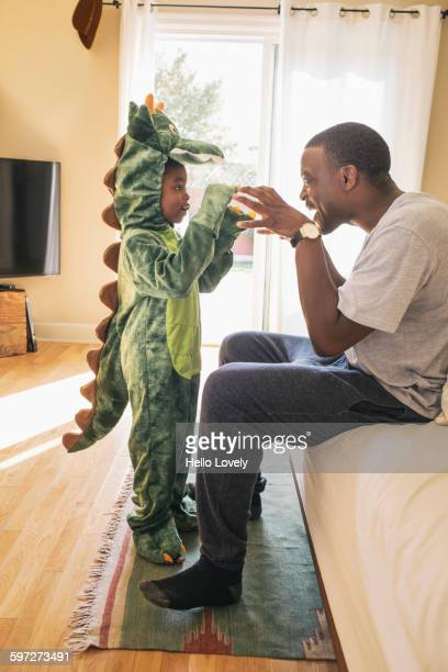 African American father playing with daughter in costume