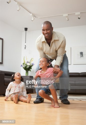 African American Living Room Apartment Decor: African American Father Playing With Daughters In Living