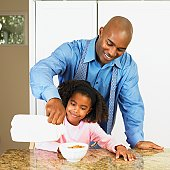African American father pouring milk into daughter's cereal