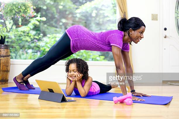 African American female doing yoga with her daughter