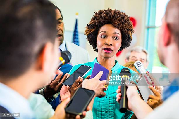 African American female political candidate surrounded by reporters