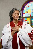 African American female Reverend with hands on heart