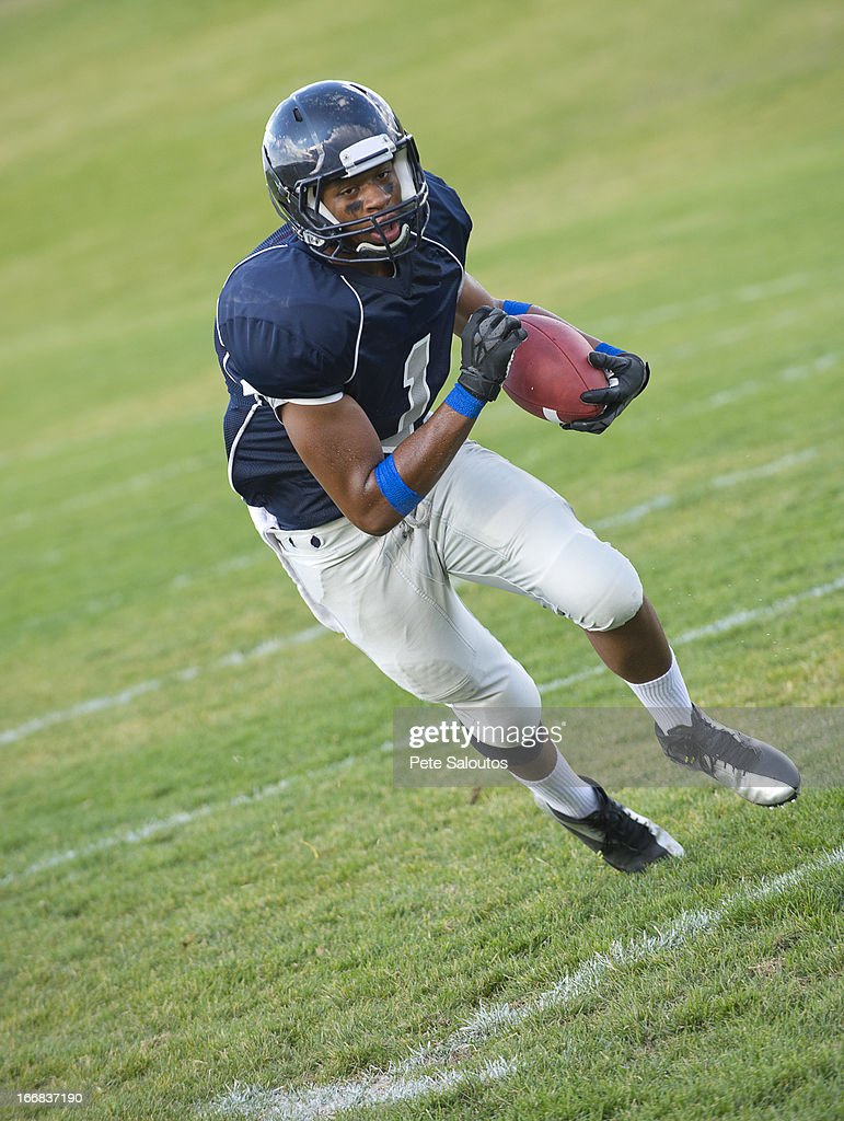 African American football player carrying ball