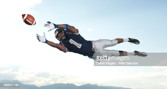 African American football player catching ball