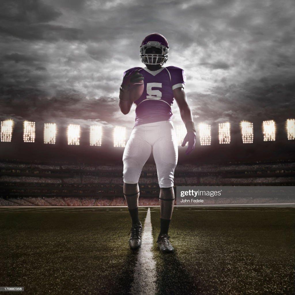African American football player illuminated on field