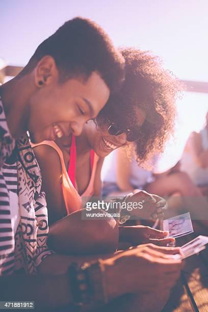 African American amis à la recherche de photographies ensemble à la plage