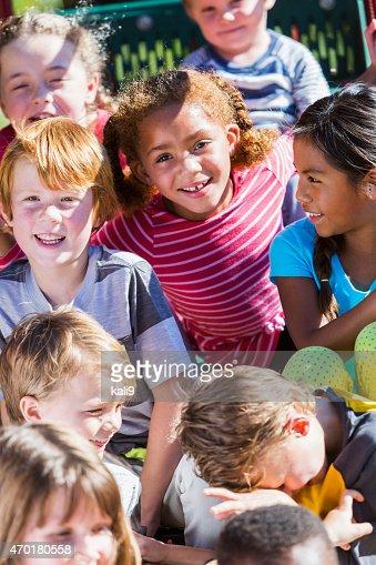 African American ragazza e gruppo di amici in un parco giochi