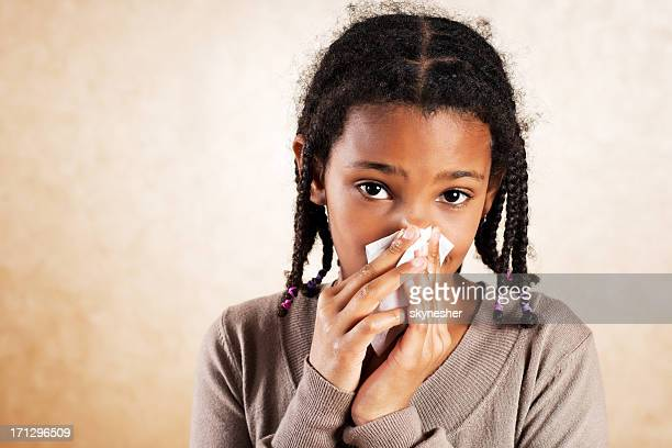 African American girl blowing her nose.
