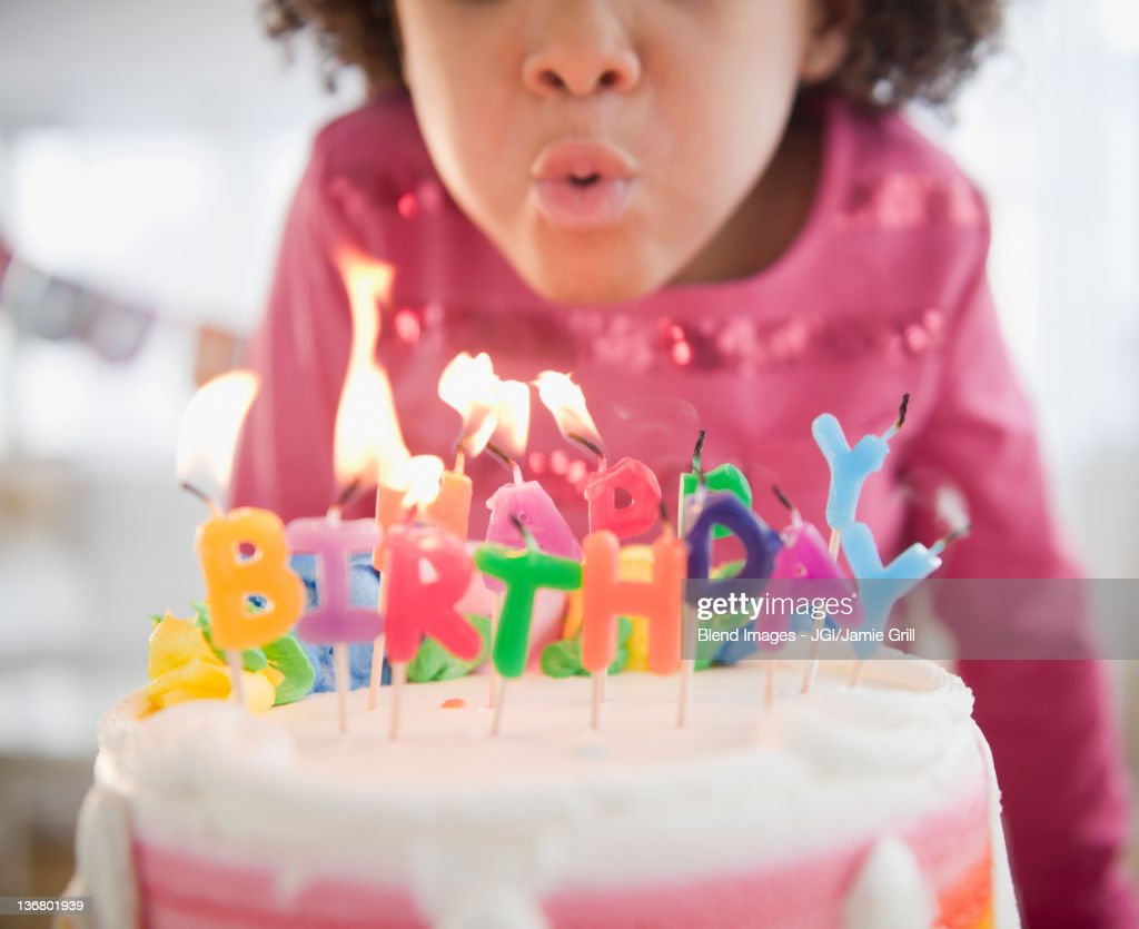 African American girl blowing out birthday candles : Stock Photo