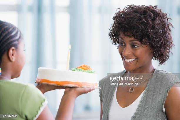 African American girl bringing mother birthday cake