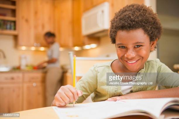 African American girl doing homework in kitchen