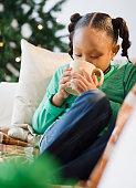 African American girl drinking hot chocolate on sofa
