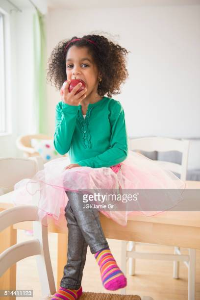 African American girl eating apple at kitchen table