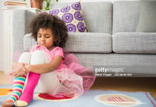 African American girl frowning in living room