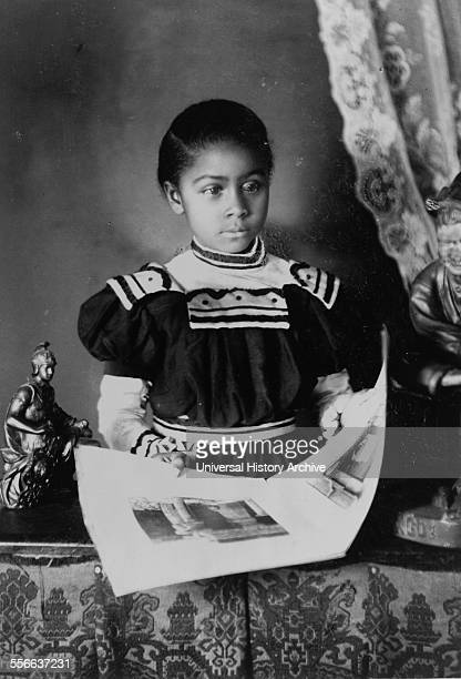 African American girl halflength portrait standing at table with illustrated book facing slightly right Types of American Negroes compiled and...