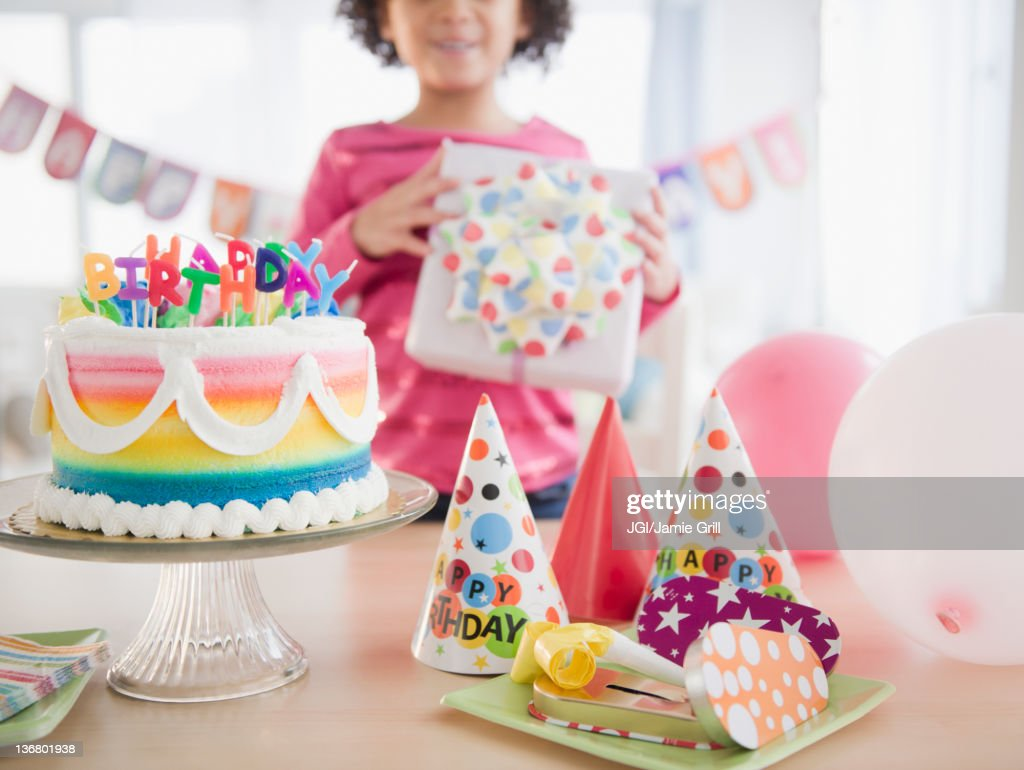 African American girl holding gift at birthday party : Stock Photo