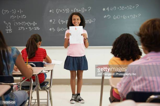 African American girl holding paper in front of class