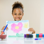 African American girl holding up painting