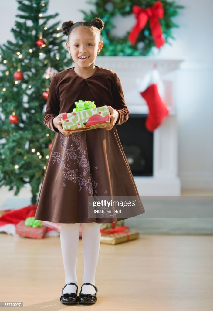 African american girl in dress holding christmas gift