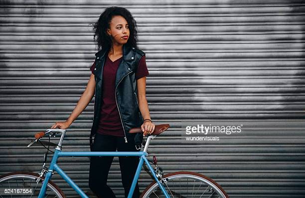 African American girl in front of graffitti with a bicycle