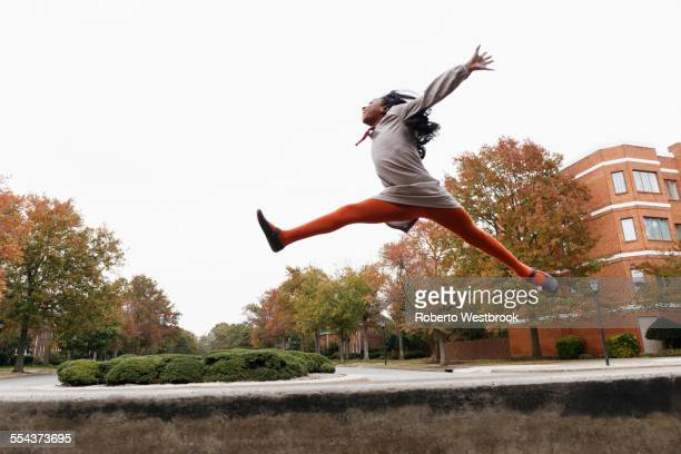 African American girl jumping for joy on suburban street