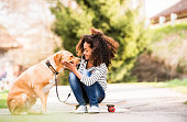 Beautiful african american girl with curly hair outdoors with her cute dog, sitting on skateboard.