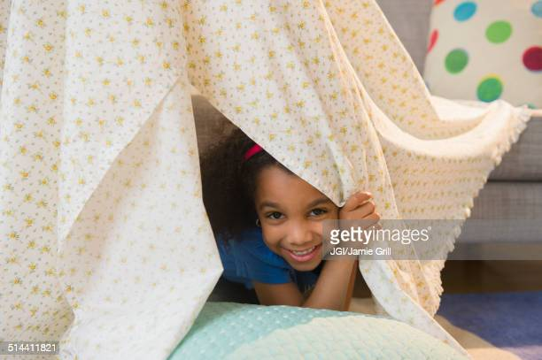 African American girl playing in blanket fort