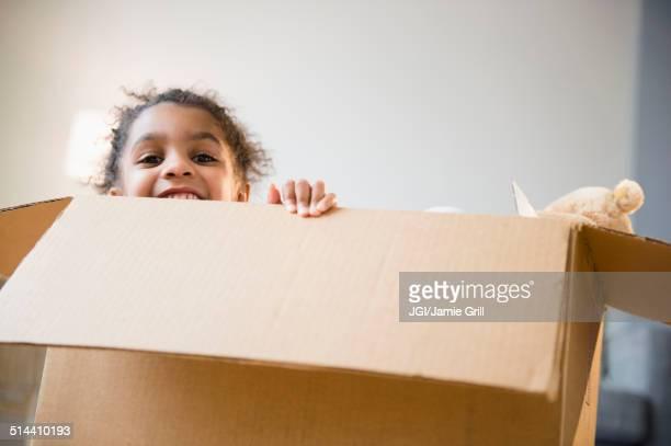 African American girl playing in cardboard box