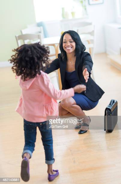 African American girl running to greet mother
