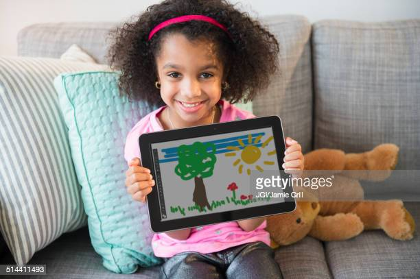 African American girl showing drawing on tablet computer