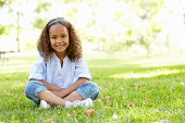 African American Girl Sitting In Park Smiling At Camera