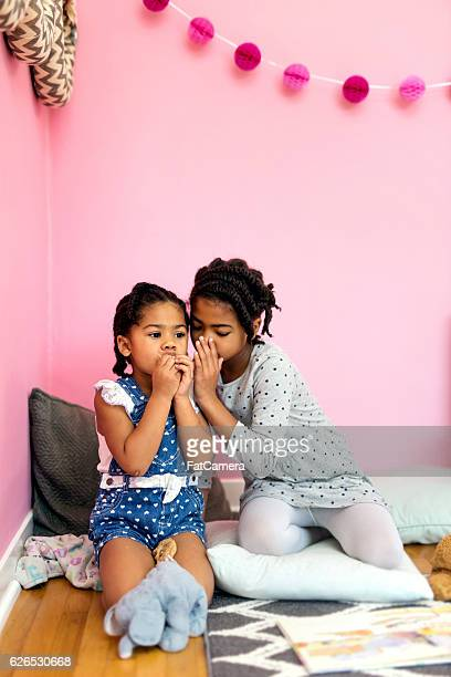African American girl telling younger sister a secret