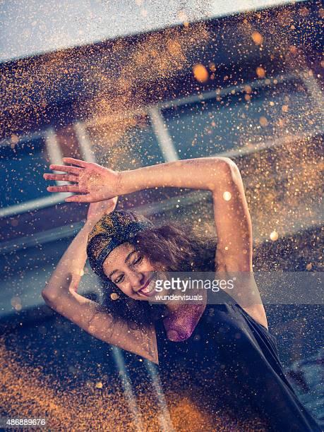 Afroamerikanische Mädchen werfen gold glitter auf der Straße