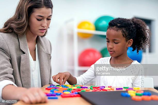 African American girl using alphabet letters for therapy